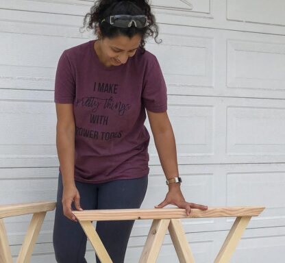 Woman working on wood with tshirt that says I make pretty things with power tools
